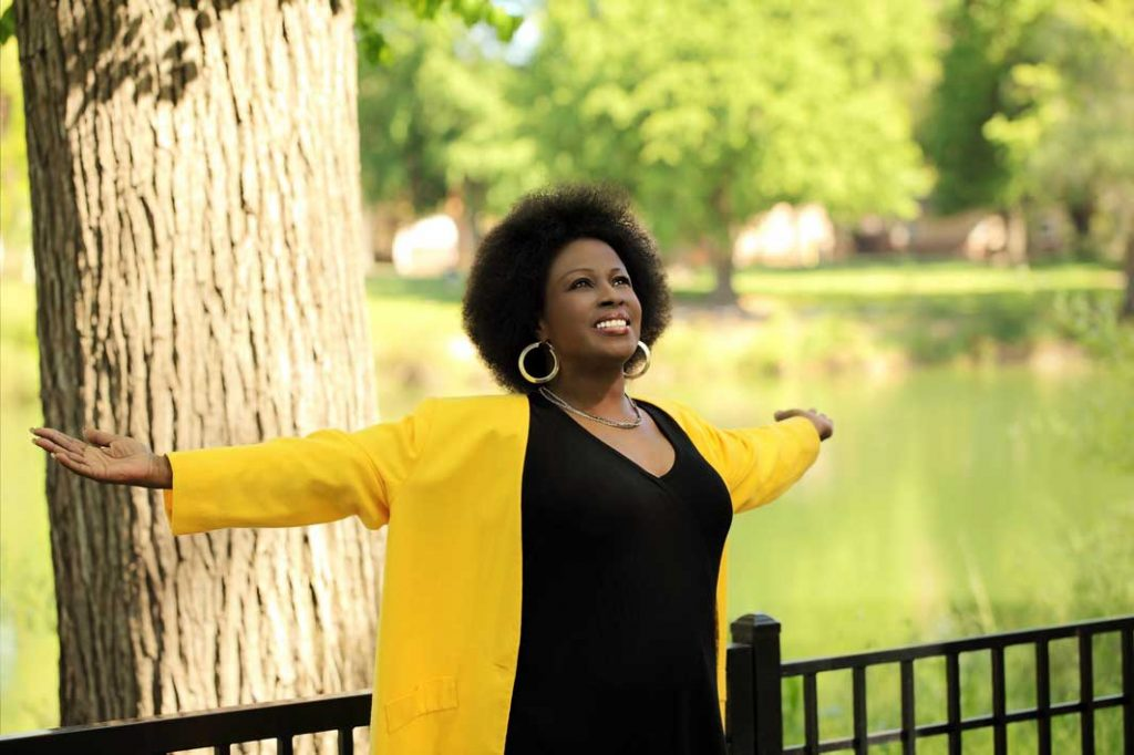 Middle Aged African American Woman with her arms outstretched celebrating life